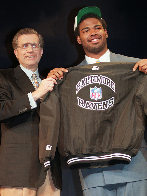 UCLA tackle Jonathan Ogden holds a Baltimore Ravens jacket with NFL Commissioner Paul Tagliabue after being selected fourth in the  NFL draft in New York  Saturday, April 20, 1996. (AP Photo/Wally Santana)
