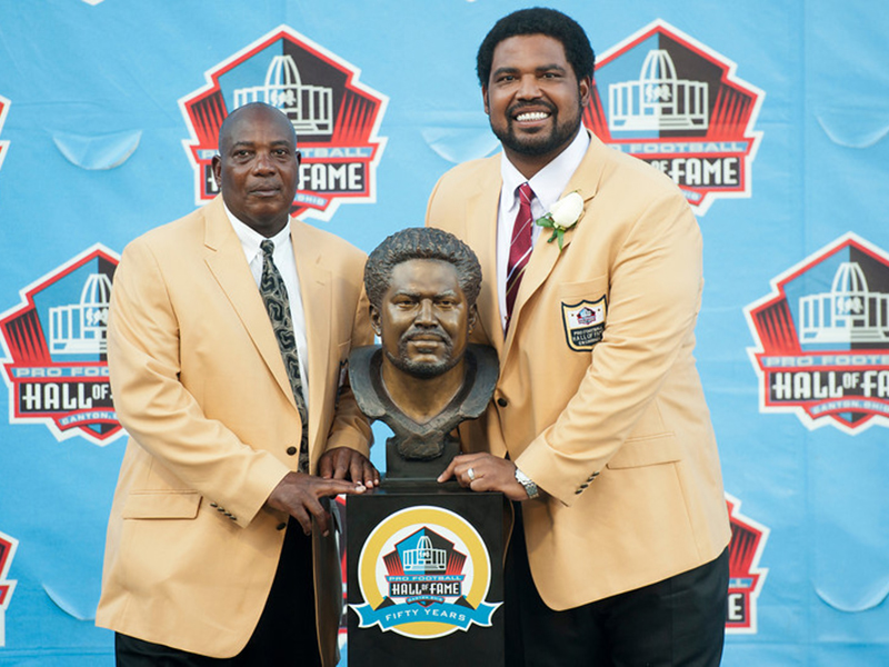 CANTON, OH - AUGUST 3: Baltimore Ravens General Manager/Executive Vice President and Hall of Fame tight end, Ozzie Newsome (L), presents former offensive lineman Jonathan Ogden of the Baltimore Ravens with his Hall of Fame bust during the NFL Class of 2013 Enshrinement Ceremony at Fawcett Stadium on Aug. 3, 2013 in Canton, Ohio. (Photo by Jason Miller/Getty Images)